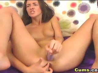 Hot slim and pretty brunette babe strokes a huge purple dildo deep inside her...