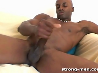 A horny black muscle stud jerking off.