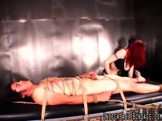 Flame-haired dominatrix Berlin strokes her pussy with a vibe beside her bound...