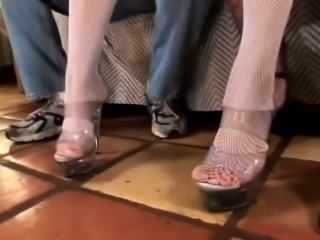 Two chicks in stockings take turns giving him a sexy foot job