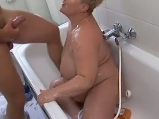 Disgusting fat blondie blows stiff dick of young man in bathroom